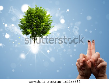 Happy finger smileys faces on hand with green magical glowing tree