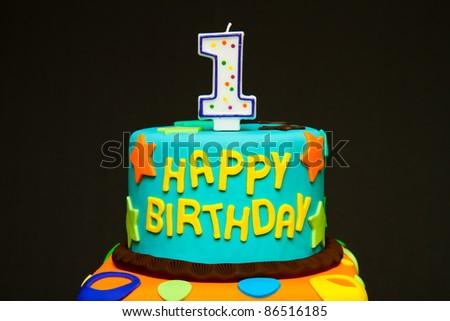 Happy first birthday fondant cake on a dark background - stock photo