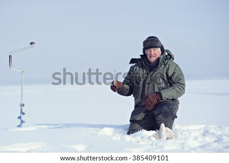 Happy fisherman caught a lot of fish. Winter fishing. The fisherman catches fish in the ice hole. - stock photo