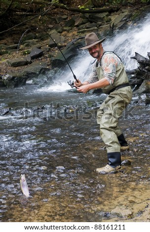 Happy fisherman caught a rainbow trout to the bait - stock photo