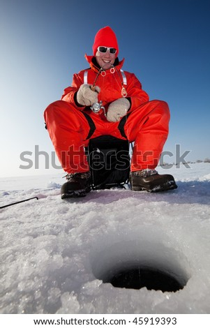 Happy fisherman fighting a fish while ice fishing