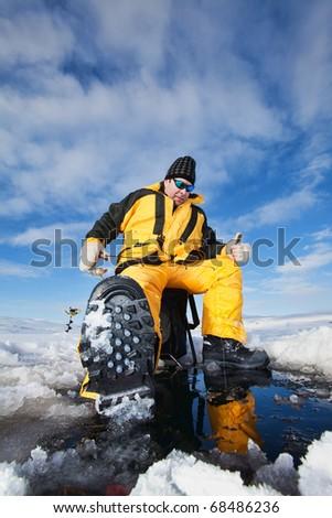 Happy fisherman in winter ice fishing - stock photo