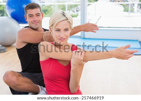 Happy fit couple working in fitness studio - stock photo