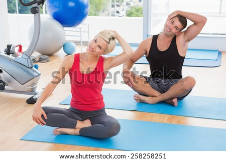 Happy fit couple working on exercise mat in fitness studio - stock photo