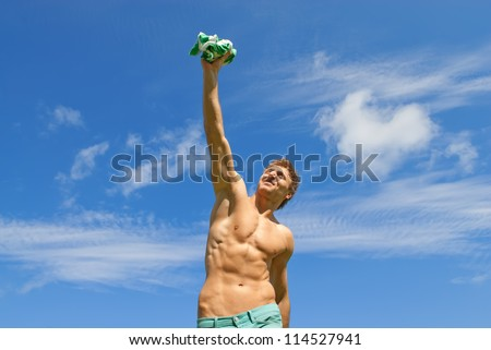 Happy fit guy with his arm raised in joy, holding his t-shirt. - stock photo