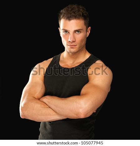 Happy fit male with arms crossed posing over black background - stock photo