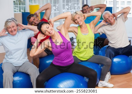 Happy fit people on fitness balls exercising in gym class - stock photo