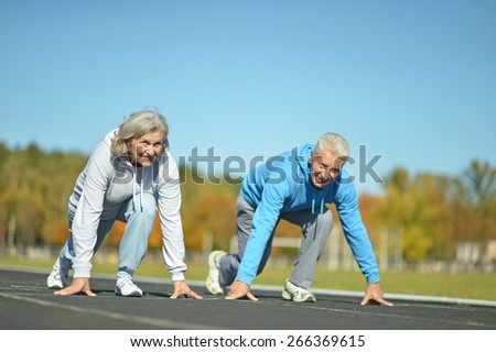 Happy fit senior couple jogging at stadium - stock photo
