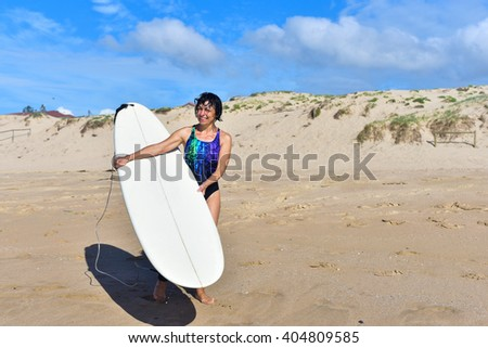 Happy fit sporty senior surfer woman wearing a swimsuit, holding her mini malibu surfboard and getting ready for a second surf session, smiling with toothy smile.  - stock photo