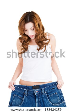 Happy fit woman with big pants, showing how much weight she lost. isolated on white.  - stock photo