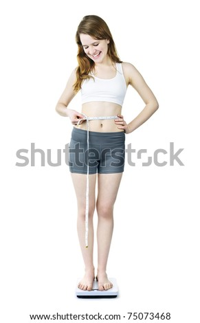 Happy fit young woman measuring waist with tape on bathroom scale isolated