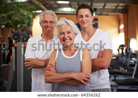 Happy fitness group standing with arms crossed in a gym - stock photo