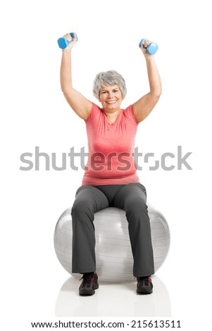 Happy fitness old woman lifting dumbbells while sitting over a PIlates ball