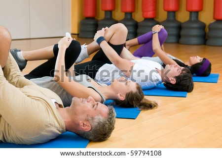 Happy fitness people class in a row doing some aerobic stretching after workout at gym - stock photo
