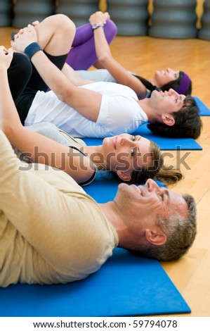 Happy fitness people in a row doing some aerobic stretching after workout at gym - stock photo