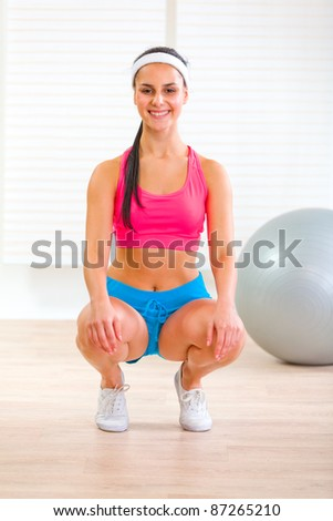 Happy fitness pretty girl squatting down at living room