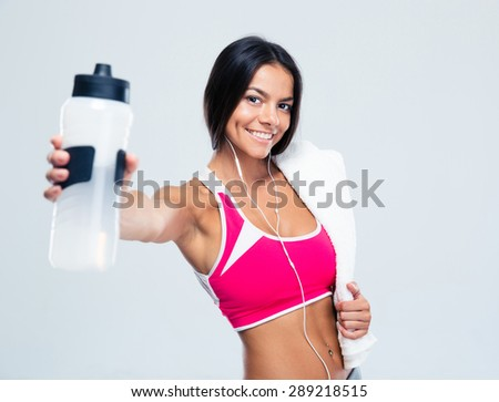 Happy fitness woman holding bottle with water over gray background. Looking at camera - stock photo
