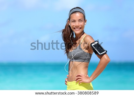 Happy fitness woman living a fit healthy lifestyle. Young Asian Caucasian girl wearing activewear and sports armband for phone and earphones, tech gear for running or cardio workout on beach. - stock photo