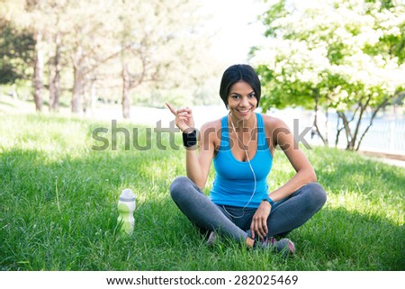 Happy fitness woman sitting on the green grass outdoors in park - stock photo