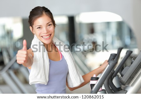 Happy fitness woman thumbs up in gym during exercise training on moonwalker treadmill. - stock photo