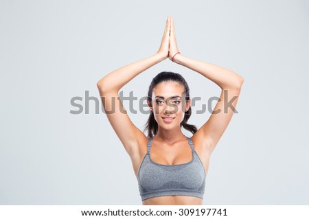 Happy fitness woman with joined hands over head isolated on a white background. Looking at camera