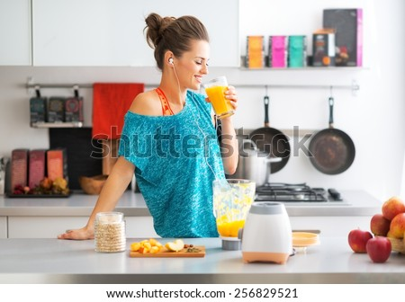 Happy fitness young woman drinking pumpkin smoothie in kitchen - stock photo