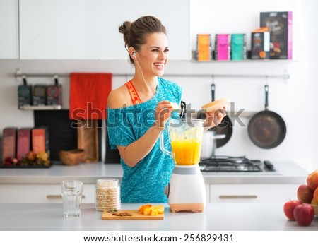 Happy fitness young woman making pumpkin smoothie in kitchen - stock photo