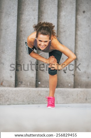 Happy fitness young woman stretching outdoors in the city - stock photo