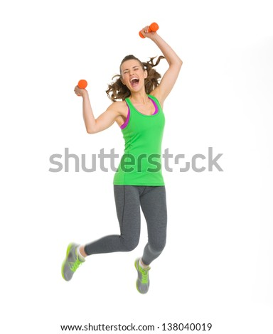 Happy fitness young woman with dumbbells jumping - stock photo