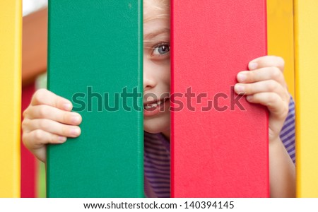 Happy five years old blond caucasian child girl looking through the colorful fence on the playground - stock photo