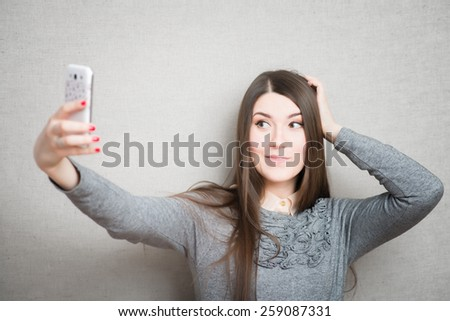 Happy flirting young girl taking pictures of herself through cell phone - stock photo