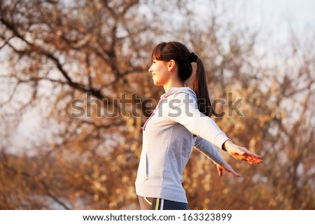 Happy flying middle-aged woman looking at the sunset, arms outstretched to the sides. Healthy lifestyle concept. Freedom and fun. - stock photo