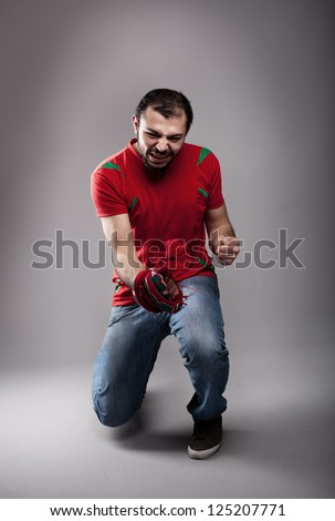 happy football fan cheering for his team - stock photo