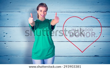Happy football fan in green against painted blue wooden planks