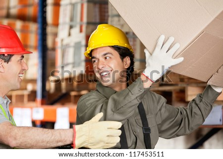 Happy foreman with coworker lifting cardboard box at warehouse - stock photo