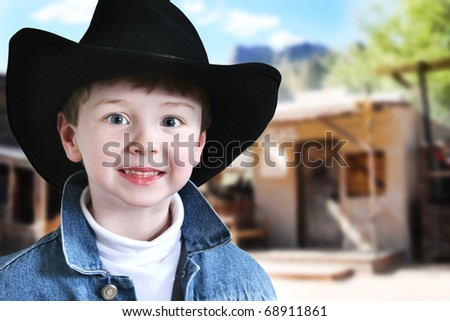 Happy four year old boy in cowboy hat and denim jacket in the old west.