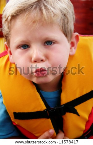 Happy four year old boy wearing a life jacket - stock photo