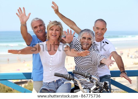 happy foursome gone for a ride by oceanfront - stock photo