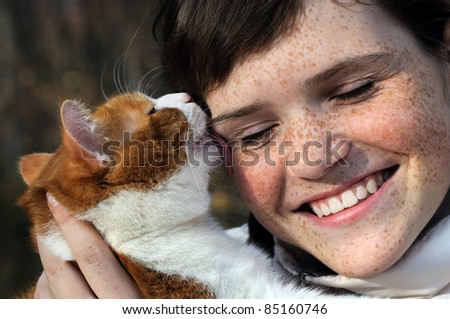 happy freckled girl and funny red cat outdoors - stock photo