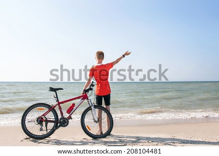 Happy free teen is standing with bicycle on a background of the sea. Caucasian boy is enjoying nature. Young active male model. Summer day. Freedom, happiness, enjoyment, travel concept.Copy space.