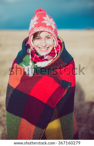 Happy free woman carefree in autumn or winter under a warm blanket enjoying the sun. Beautiful Caucasian girl outdoors.