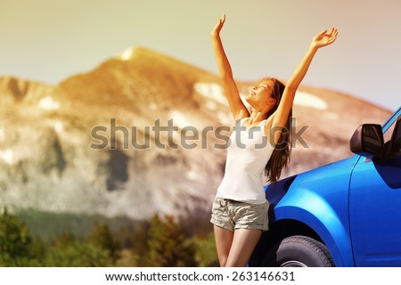 Happy free woman next to car relaxing on summer road trip adventure travel with open arms up showing freedom. Nature travel concept with mountain background in the USA. Young Asian adult driver. - stock photo