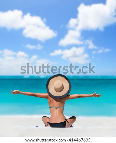 Happy freedom carefree bikini woman enjoying summer beach vacation with arms up cheering in success. Girl feeling free with sun hat relaxing sunbathing on holidays. Caribbean south tropical travel. - stock photo