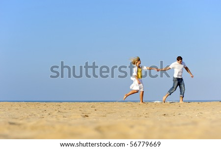 Happy, fresh young couple enjoy a day on the beach together
