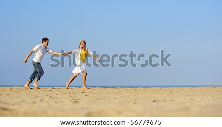 Happy, fresh young couple enjoy a day on the beach together - stock photo