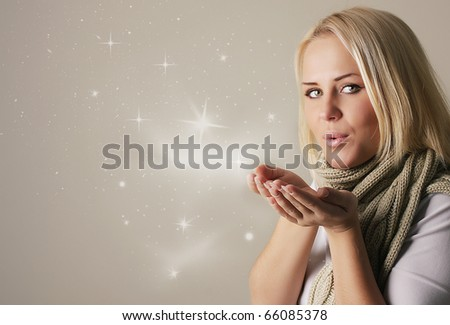 Happy friendly woman blowing snowflakes in winter season - stock photo