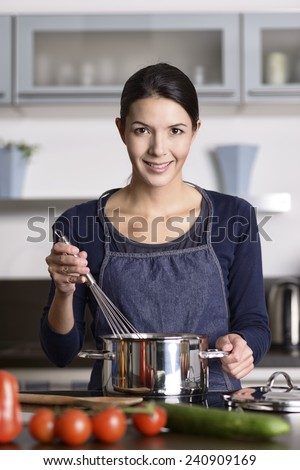 Happy friendly young housewife cooking dinner standing at the hob holding a whisk over a saucepan as she prepares the fresh vegetables for dinner while giving the camera a lovely smile - stock photo