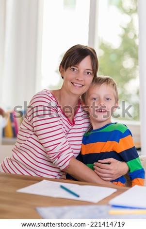 Happy friendly young mother and son posing together doing paperwork at a table at home looking at the camera with big warm smiles - stock photo