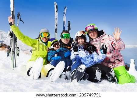 Happy friends after skiing sit on snow wave hands