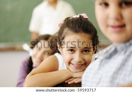 Happy friends and colleagues in classroom, male and female, smiling - stock photo